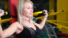 Young fitness model works out on training apparatus inside in fitness center Stock Footage