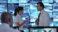4K Surveillance team having discussion in control room with multiple screens Stock Footage