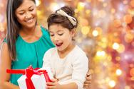 Happy mother and girl with gift box over lights Stock Photos