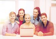 Smiling students with laptop at school Stock Photos