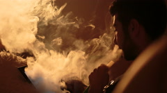 Man smokes a hookah and uses tablet Stock Footage