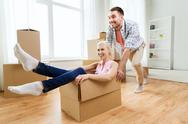 Couple with cardboard boxes having fun at new home Stock Photos