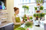 Smiling florist woman making bunch at flower shop Stock Photos