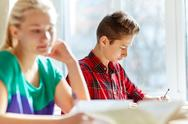 Group of students with books writing school test Stock Photos