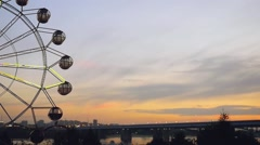 Ferris wheel at sunset on promenade in slowmotion.  Stock Footage