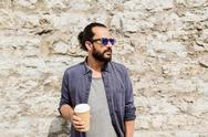 Man drinking coffee from paper cup on street Stock Photos