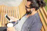 Man with earphones and smartphone drinking coffee Stock Photos