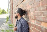 Man with backpack standing at city street wall Stock Photos