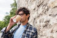 Man in eyeglasses drinking coffee over street wall Stock Photos