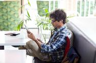 Man with tablet pc and earphones sitting at cafe Stock Photos