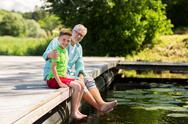 Grandfather and grandson sitting on river berth Stock Photos