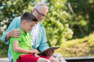 Happy grandfather and boy with tablet pc outdoors Stock Photos