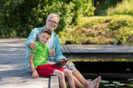 Grandfather and boy with tablet pc on river berth Stock Photos