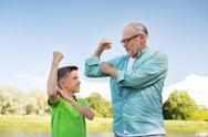 Happy grandfather and grandson showing muscles Stock Photos