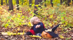 Halloween baby boy. Child in autumn forest looking at the falling leaves. Stock Footage