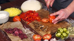 Mens hands cut pizza ingredients on bamboo cutting board for cooking pizza. Stock Footage