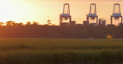 Industrial Ship Cranes at Sunset with Marsh Stock Footage