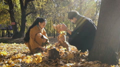 Happy family playing with autumn leaves in park. Mom and dad throw leas up in Stock Footage
