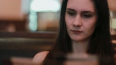 Closeup view of a young beautiful longhaired woman looking through the menu in Stock Footage