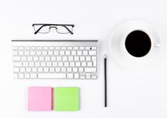 White keyboard with glasses and sticky note paperson white background Stock Photos