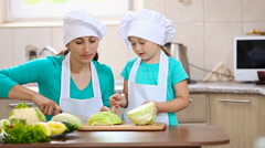 Mother with her daughter cut cabbage Stock Footage