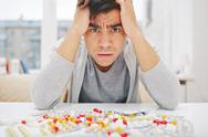 Anxious young man looking at camera with assortment of tranquilizers near by Stock Photos