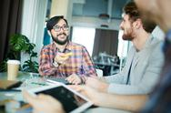 Young designer consulting with colleagues at meeting Stock Photos