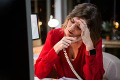 Stressed businesswoman talking on phone at her desk Stock Photos