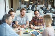 Confident employees having discussion of ideas Stock Photos