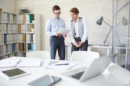 Two businessmen discussing documents in office Stock Photos