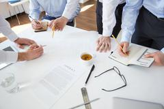 Group of architects planning their work by desk Stock Photos