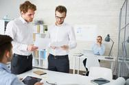Two engineers with papers brainstorming in office Stock Photos