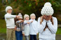 Upset girl crying while group of kids bullying her Stock Photos