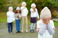 Little boy crying with his face in hands on background of bullying children Stock Photos