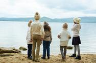 Group of friendly schoolchildren standing on sand and looking at river Stock Photos