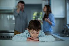 Upset boy sitting while couple having argument in background Stock Photos