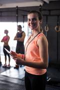 Portrait of happy female fitness instructor holding clipboard in gym Stock Photos
