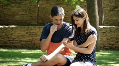 Young man and woman talking on a bench, vaping e-cig, slow motion  2 Stock Footage