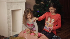 Two little sisters decorating Christmas tree with fir-cone. New year preparation Stock Footage