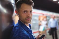 Portrait of handsome man listening song on mobile phone Stock Photos