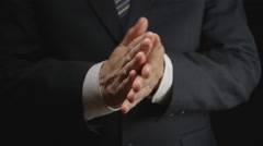 Businessman in a suit rubs hands Stock Footage