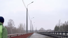 Man jogging on bridge in dull weather Stock Footage