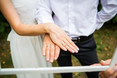 Newly wed couple's hands with wedding rings Stock Photos
