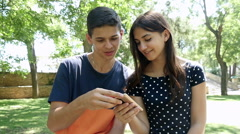 Young couple with smartphone sitting on a bench in the park, slow motion 1 Stock Footage