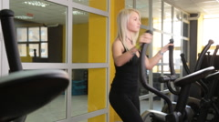 Young woman exercising on elliptical trainer Stock Footage