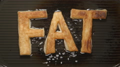 FAT letters fry in oil on a grill (top view) Stock Footage