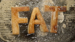 FAT letters fry in oil in a grill - boils (top view) Stock Footage