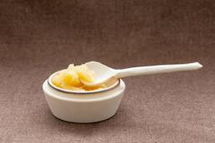 Pot of honey and wooden dipper on a sackcloth Stock Photos