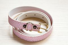 Pink women style belt on a light wooden background Stock Photos