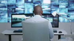 4K Security team watching CCTV screens in control room, officer talking on radio Stock Footage